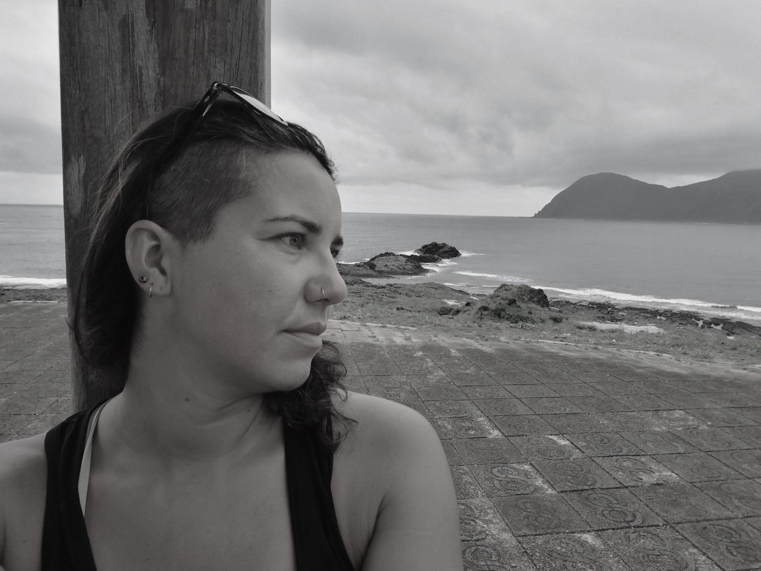 Frau nachdenklich aufs Meer blickendrau