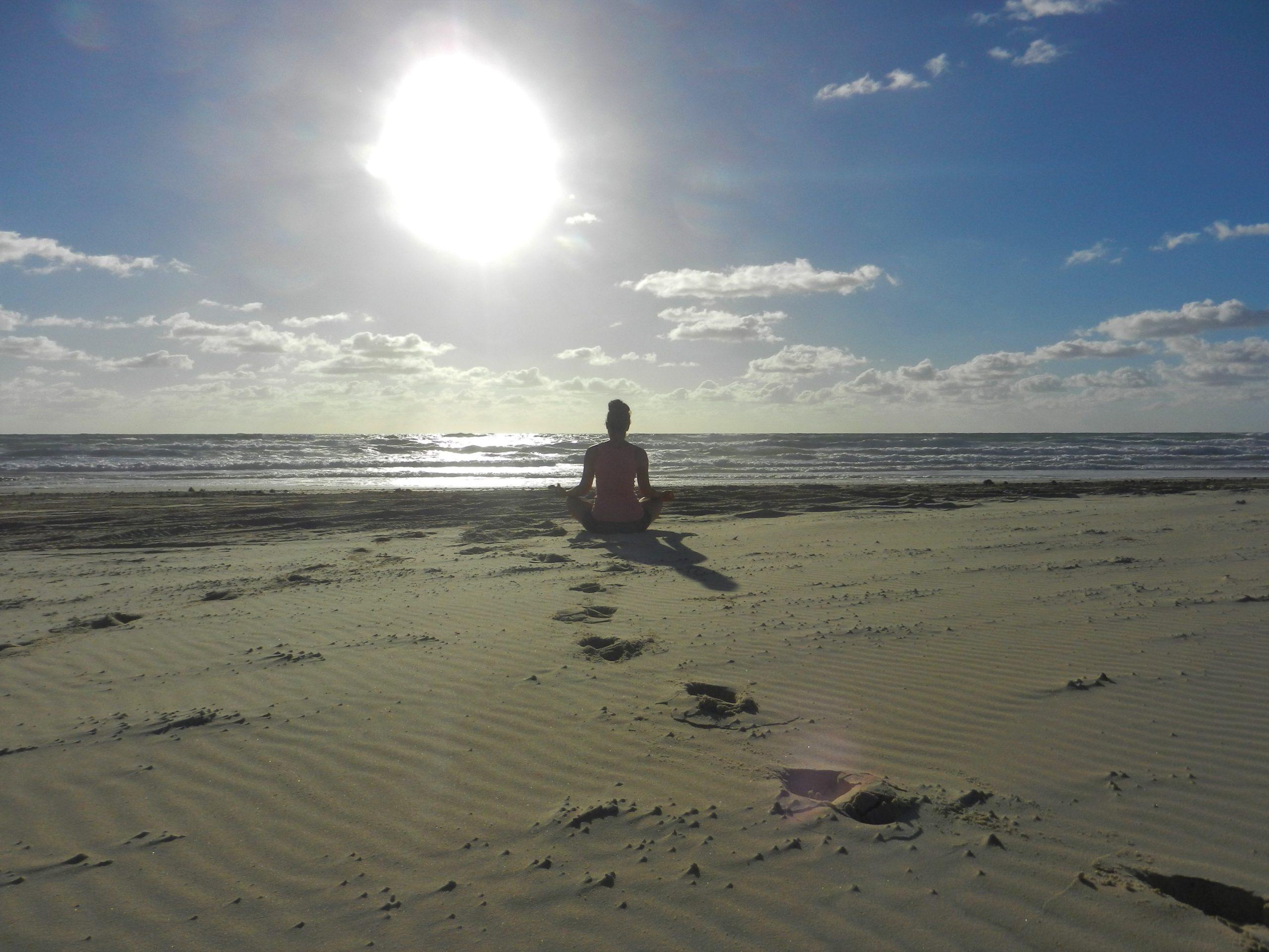 Frau meditierend beim Sonnenaufgang am Meer